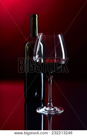 Glass And Bottle Of Red Wine On A Black Reflective Background.