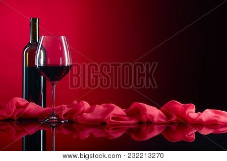Glass And Bottle Of Red Wine On A Black  Background.copy Space .