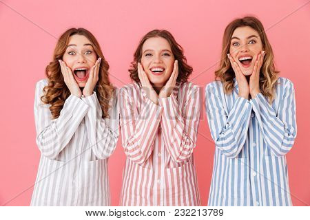 Photo of three lovely women 20s wearing colorful striped pajamas screaming in delight and touching cheeks isolated over pink background