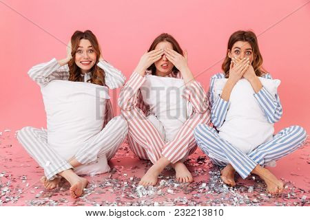 Three women in home clothings holding pillows and showing symbols of tree wise monkeys - see no evil, hear no evil, speak no evil at sleepover isolated over pink background