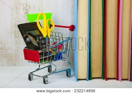 Items For School In A Shopping Cart And Books On A Wooden Background. Concept Of Buying Items For Sc
