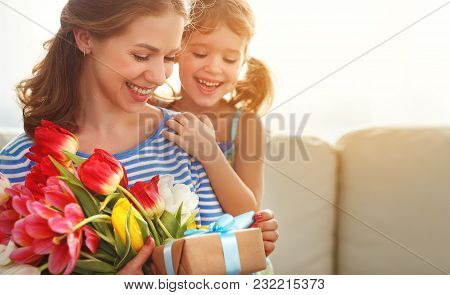 Happy Mother's Day! Child Daughter   Gives Mother A Bouquet Of Flowers To Tulips And Gift