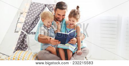 Family Father Reading To Children Book In Tent In Playroom At Home