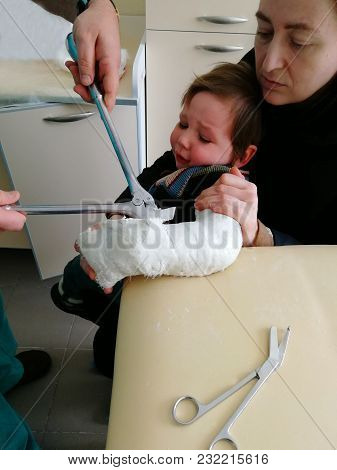 The Boy Is Removed From The Plaster, The Boy Is Held Tight, He Is Scared And Cries