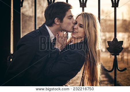 Loving Couple Hugs And Kisses At Sunset In The Sunlight And In The Reflection Of Sunlight In The Par