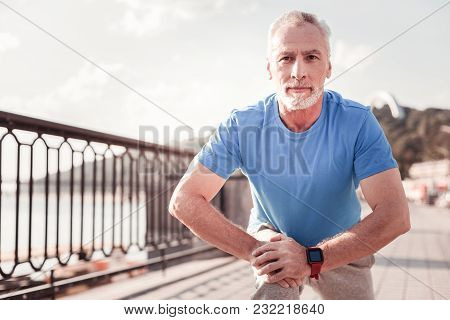 Spot In My Heart. Concentrated Senior Confident Man Making Stretch Exercises Preparing For The Train