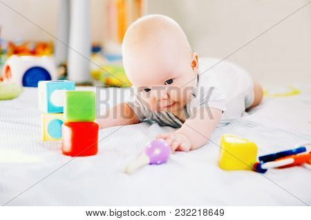 Baby Playing With Colorful Toys At Home. Happy 6 Months Old Baby Child Playing And Discovery. Early
