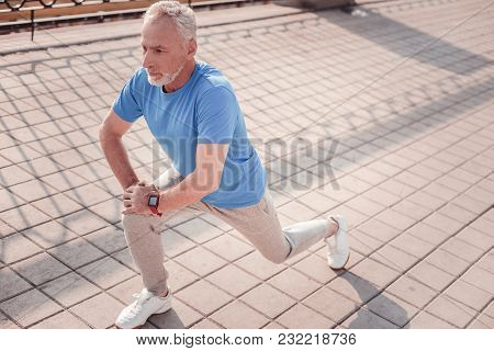 I Can. Serious Aged Focused Man Preparing For The Training Looking Straight Making Stretch Exercises