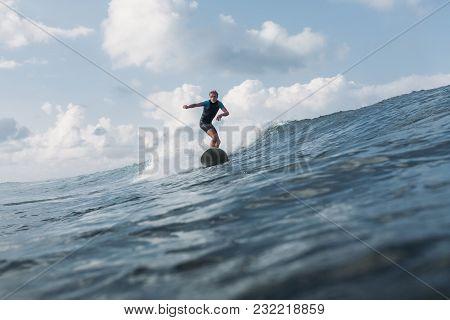 Sportsman Riding Wave On Surf Board In Ocean