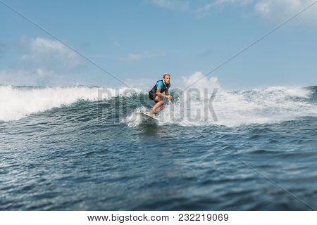 Surfer Riding Wave On Board In Ocean