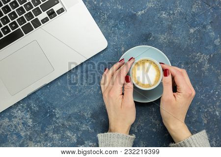 High Angle View Of Female Hand Reaching Cup Of Coffee Next To Laptop Against Blue Background