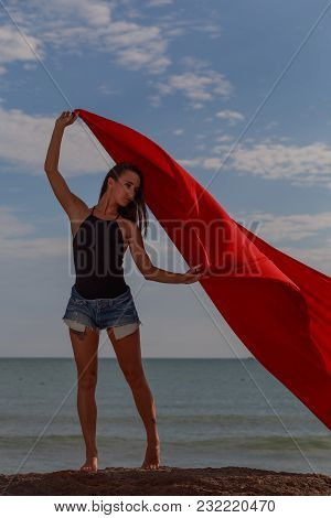 The Girl On The Beach. A Red Cloth Develops In The Wind.