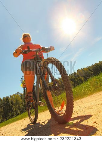 Overweight woman slimming on bicycle. Active people enjoying summer holidays on countryside.