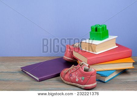 Open Book, Hardback Colorful Books, Toy, Shoes On Wooden Table. Back To School. Copy Space For Text.