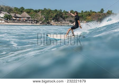Surfer Riding Wave On Surf Board In Ocean