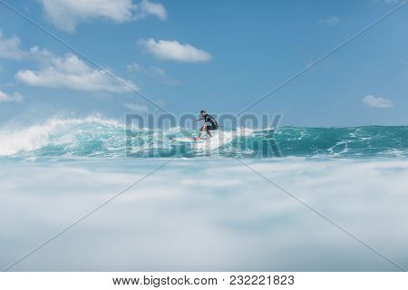 Active Man Riding Wave On Surf Board In Ocean