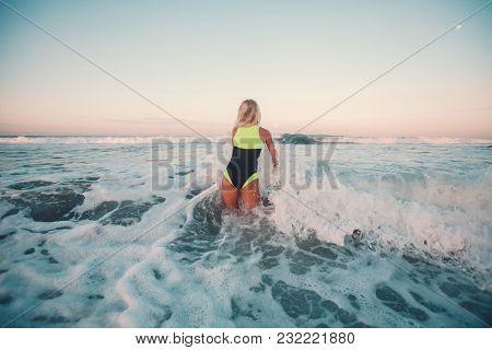 Back View Of Sportswoman Surfing On Surf Board In Ocean