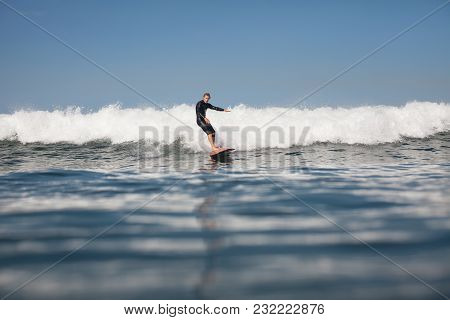 Active Surfer Having Fun And Riding Wave On Board In Ocean