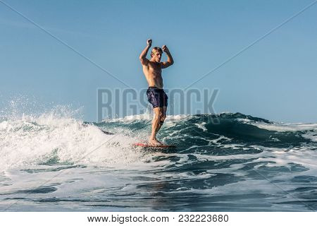 Active Surfer Having Fun And Riding Wave In Ocean