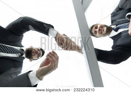 View from below. From behind the glass. Handshake of business partners