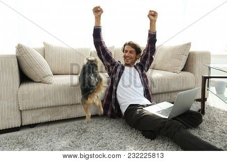 happy young man exults with his dog sitting in the living room
