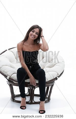 young woman sitting in a comfortable big armchair