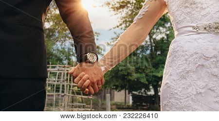 Couple Holding Hands On Their Wedding Day