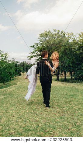 Bridegroom Carrying Beautiful Bride In His Arms