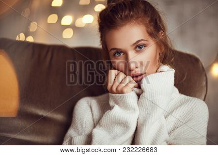 Attractive Young Woman In White Sweater Sitting On Leather Couch And Looking At Camera.
