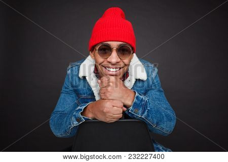 Handsome Ethnic Man In Trendy Outfit And Sunglasses Smiling Contently At Camera On Black.