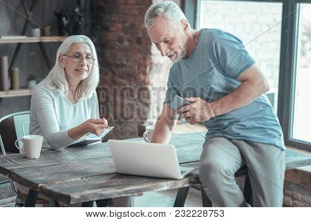 Important Task. Busy Senior Pleasant Couple Spending Time Together In The Comfortable Room Working A