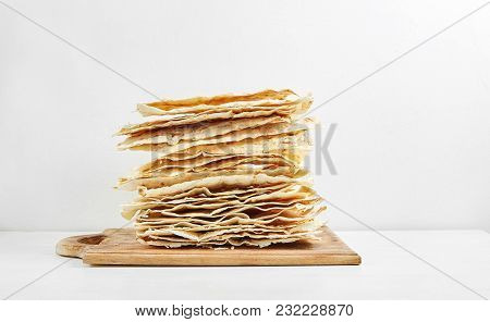 A Stack Of Plain Grilled Pita Bread On A Wooden Cutting Board With A White Background.