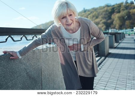 Cannot Stand This Pain. Scared Elderly Woman Feeling Intense Physical Discomfort And Holding Her Han