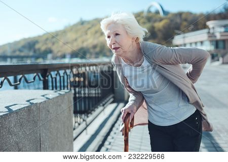 Intense Pain. Tired Elderly Lady With A Walking Cane Holding Her Hand On A Lower Back While Feeling