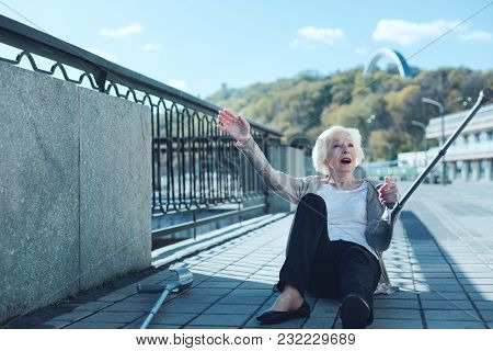 Unpleasant Accident. Frightened Elderly Woman With A Pair Of Crutches Falling To The Ground Unexpect