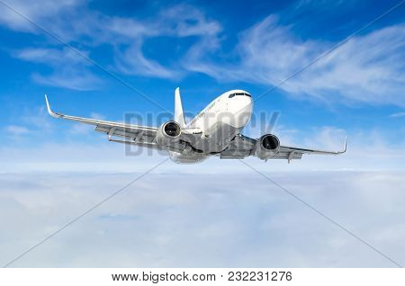 White Aircraft Flies Climbs Height, Flight Level High In The Sky Above The Clouds Blue Sky