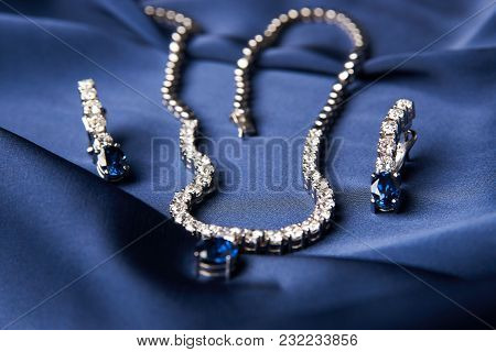 Platinum Necklace And Earrings With A Diamond And Blue Precious