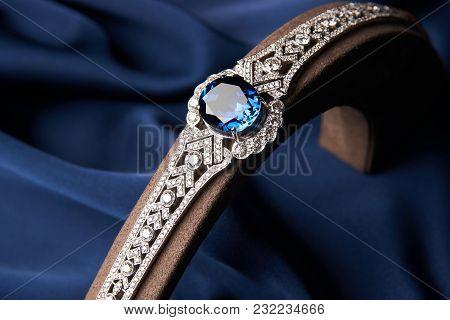 Beautiful Platinum Bracelet. Luxury Women Bracelet With Diamonds And Sapphire On Blue Silk Backgroun