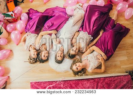 Bride With Bridesmaids Are Lying On The Floor With Pink Balloons Around. Bridedmaids In The Same Mag