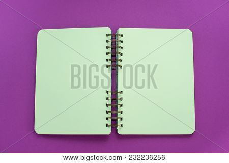 An Open Notebook On A Bright Saturated Purple Background. Flat Lay Top View