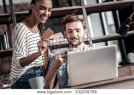 Internet Banking. Positive Nice Attractive Woman Sitting Together With Her Boyfriend And Smiling Whi