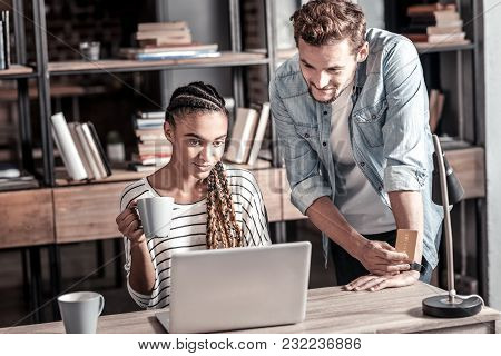 Modern Device. Nice Smart Young Woman Sitting In Front Of The Laptop And Holding A Cup Of Tea While
