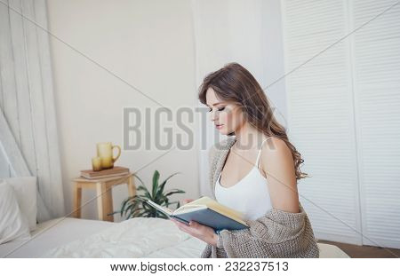 Beautiful Young Woman Reading Book At Home. Copyspace