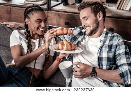 Tasty Croissant. Cheerful Positive Young Woman Holding A Croissant And Feeding Her Boyfriend While H
