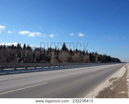 Landscape With Long Straight Empty Suburban Highway With Metal A Fence On The Sides And Forest Under