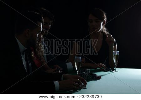 side view of group of people playing poker together in casino