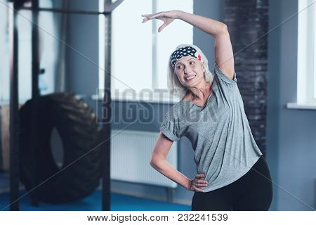 Sport Is Life. Positive Minded Woman Grinning Broadly And Looking Somewhere While Doing Side Bend Ex