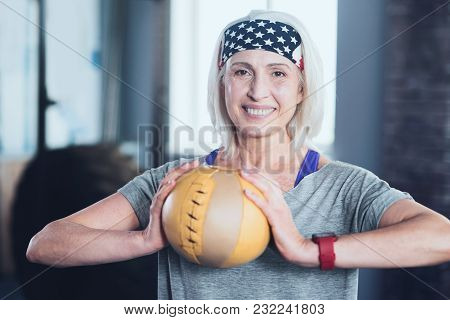 Life Goes On. Cheerful Woman Looking Into The Camera With A Broad Smile On Her Face While Exercising