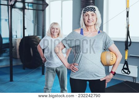 Sport Is Waiting For You. Selective Focus On A Cheerful Lady Standing With Her Hand On A Hip And Hol
