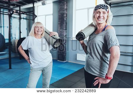 Sporty Best Friends Forever. Selective Focus On A Radiant Woman Standing With A Training Mat On Her
